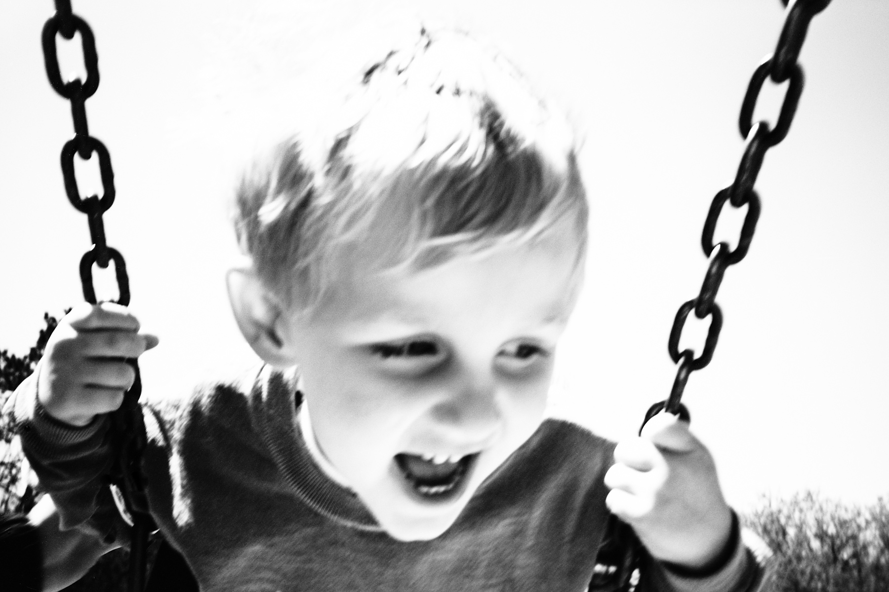 black and white photograph of child on swing in motion