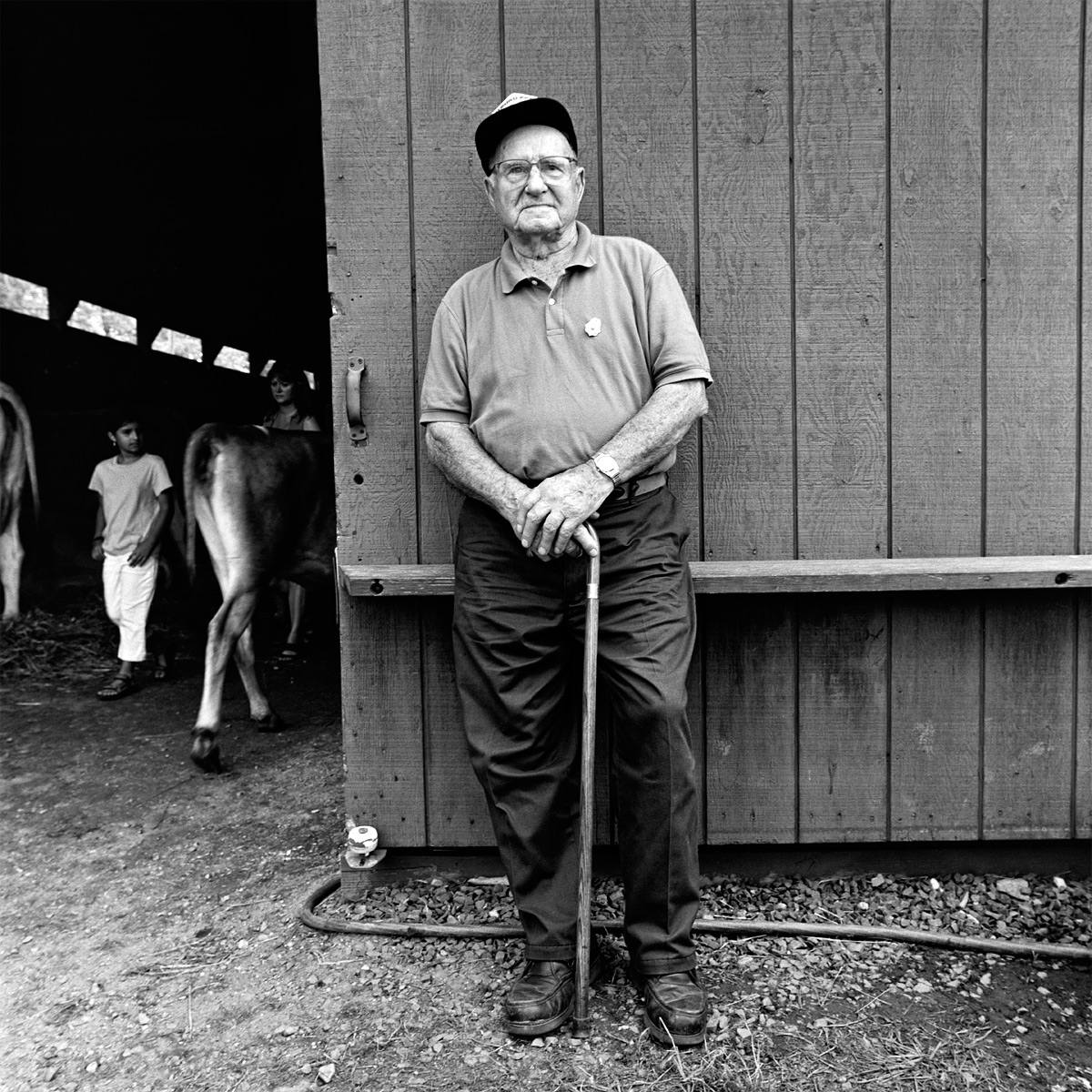 black and white photograph of old man standing in front of barn with cane