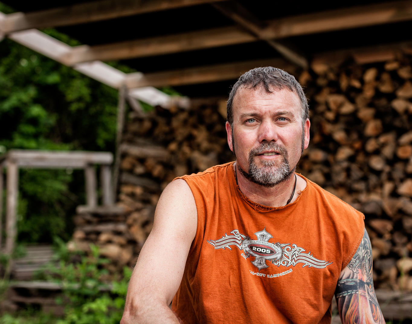 Connecticut man with Multiple Sclerosis sits in front of stacked wood pile