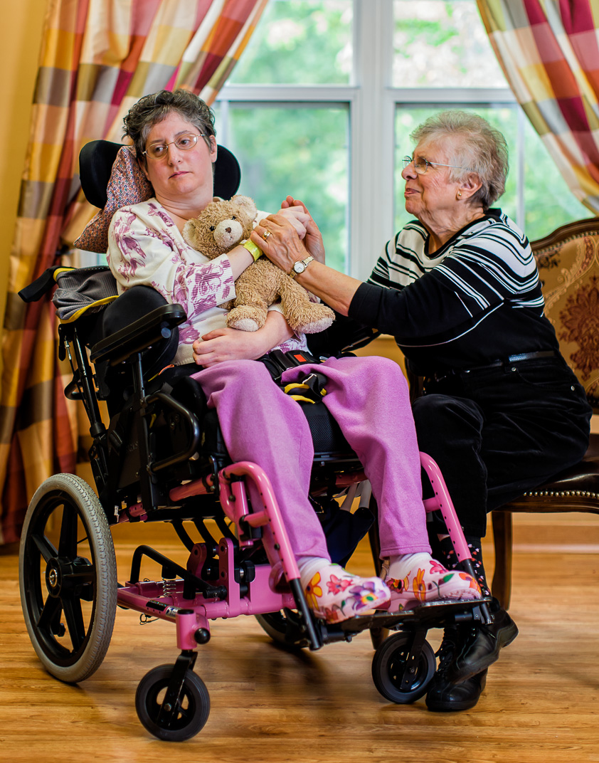 Connecticut mother embraces daughter with Multiple Sclerosis in wheelchair with teddy bear