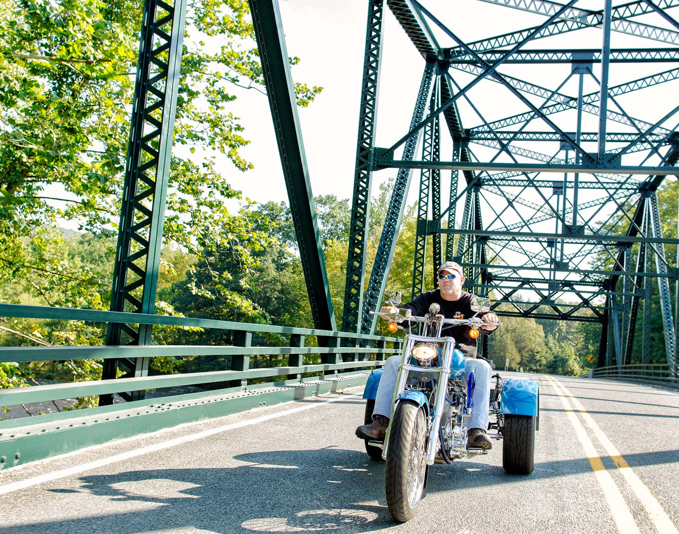 Connecticut man with Multiple Sclerosis rides modified three wheeled motorcycle over countty bridge on sunny day