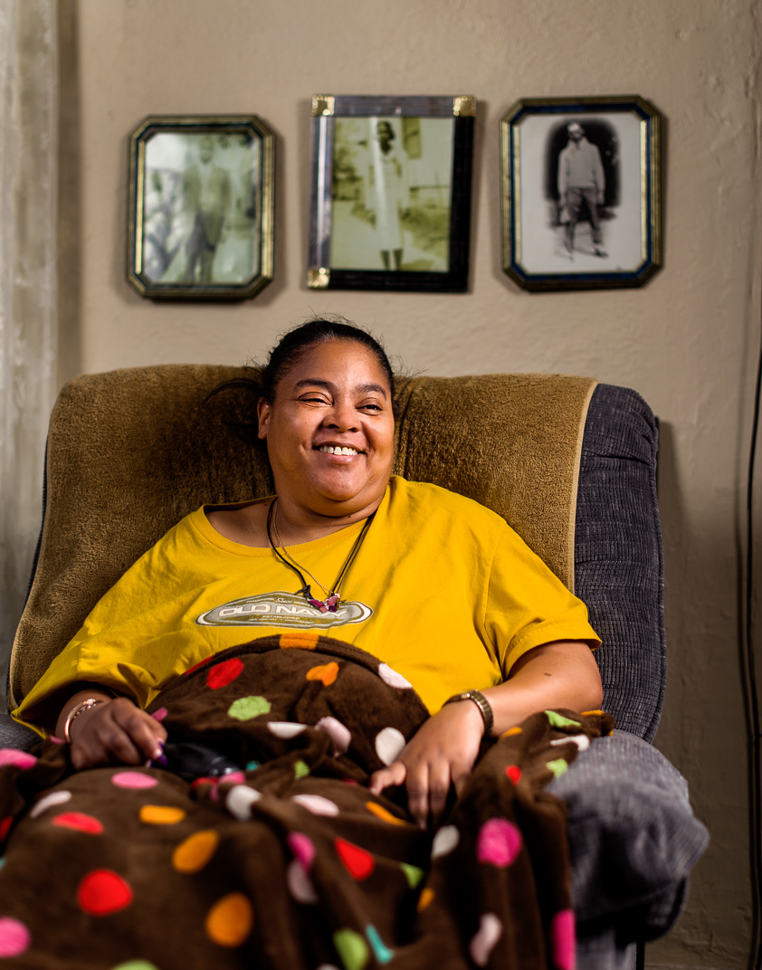 Connecticut woman with Multiple Sclerosis sits in recliner with vintage photos of family behind her