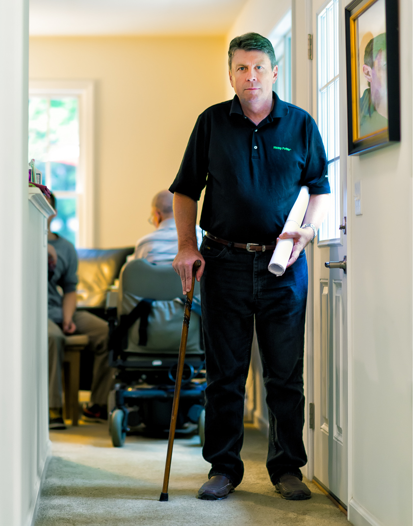 Connecticut man with Multiple Sclerosis stands with cane and blueprints in home he designed for handicap man
