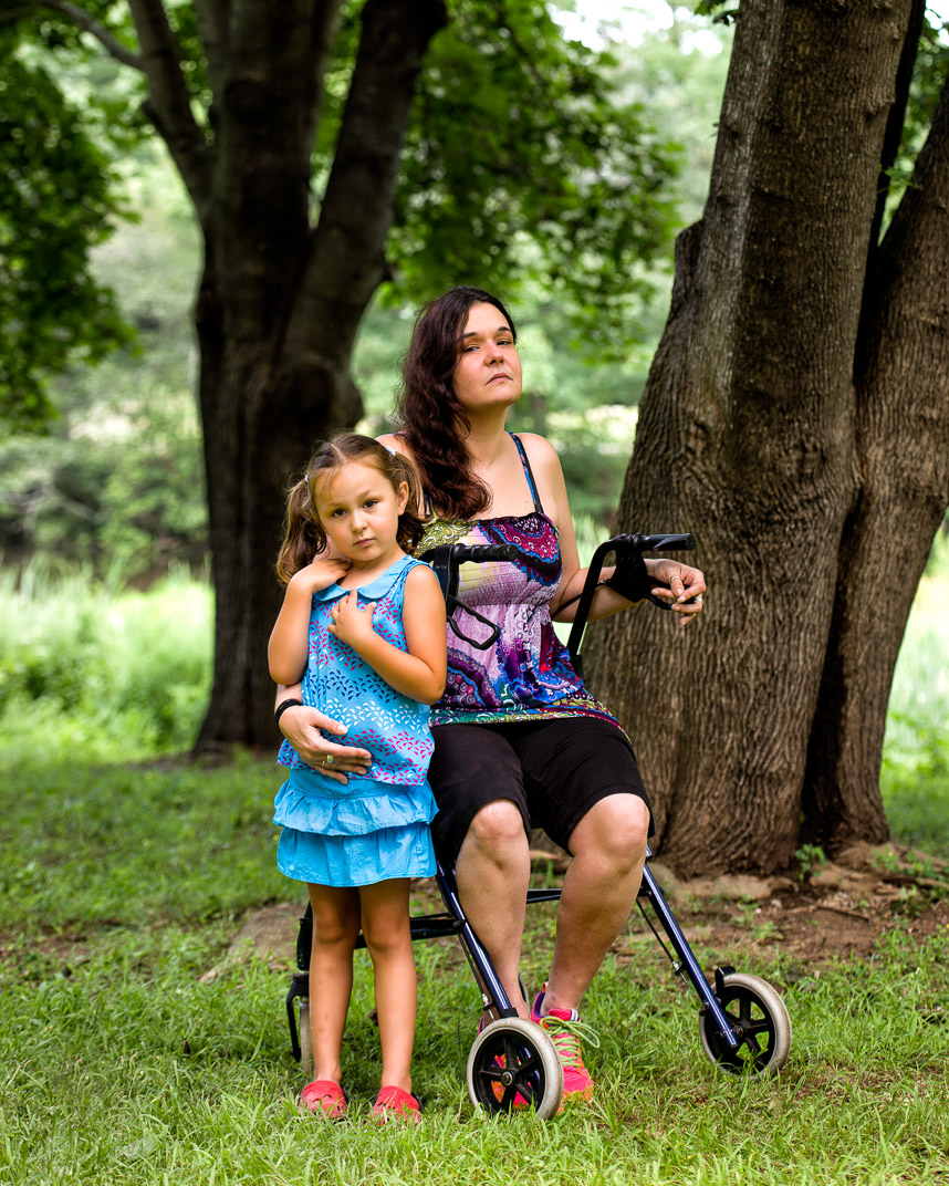 Connecticut woman with Multiple Sclerosis sits on walker with daughter by her side under large tree