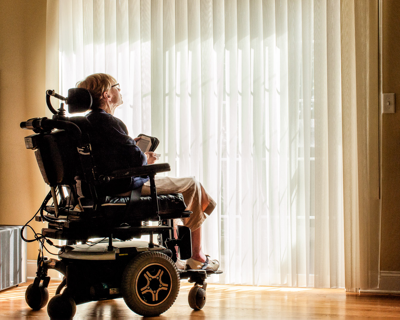 Connecitcut woman with Multiple Sclerosis sits in wheelchair in front of large bright patio window
