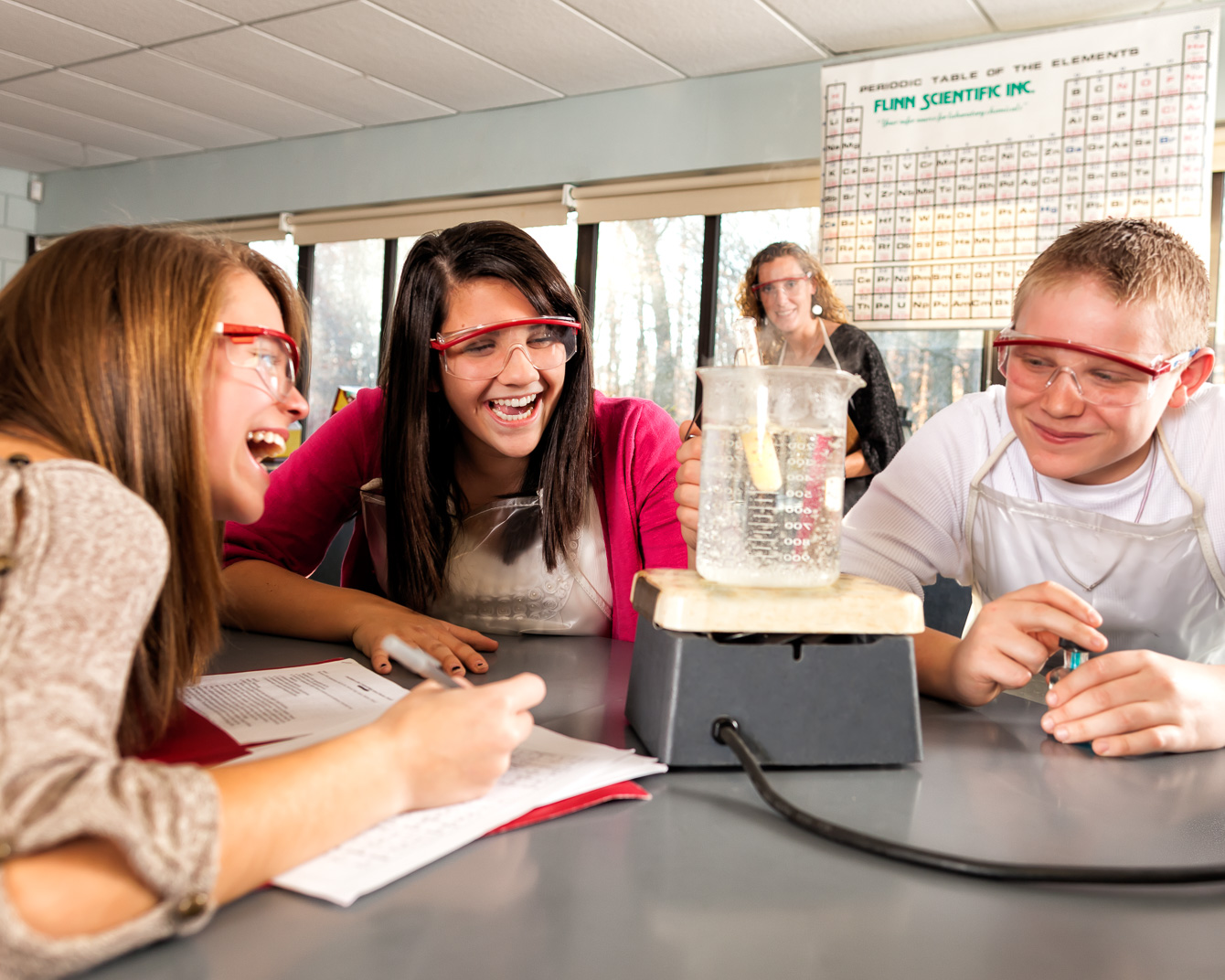 Young Connecticut woman with Multiple Sclerosis laughs with fellow students in high school chemistry class while completing experiment with bunsen burner
