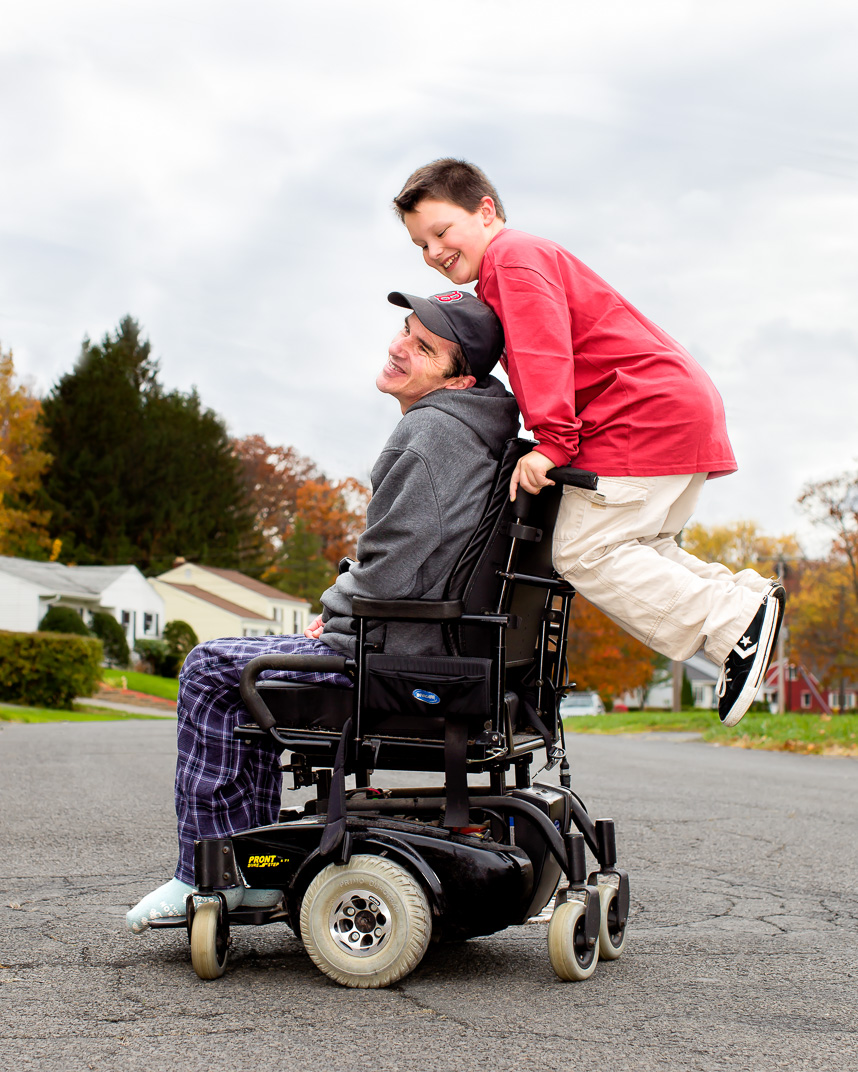 Connecticut son rides on back of fathers wheelchair who has Multiple Sclerosis in middle of suburban neighborhood