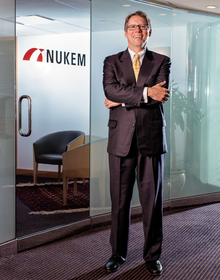 Man in suit smiling with arms crossed in front of corporate office