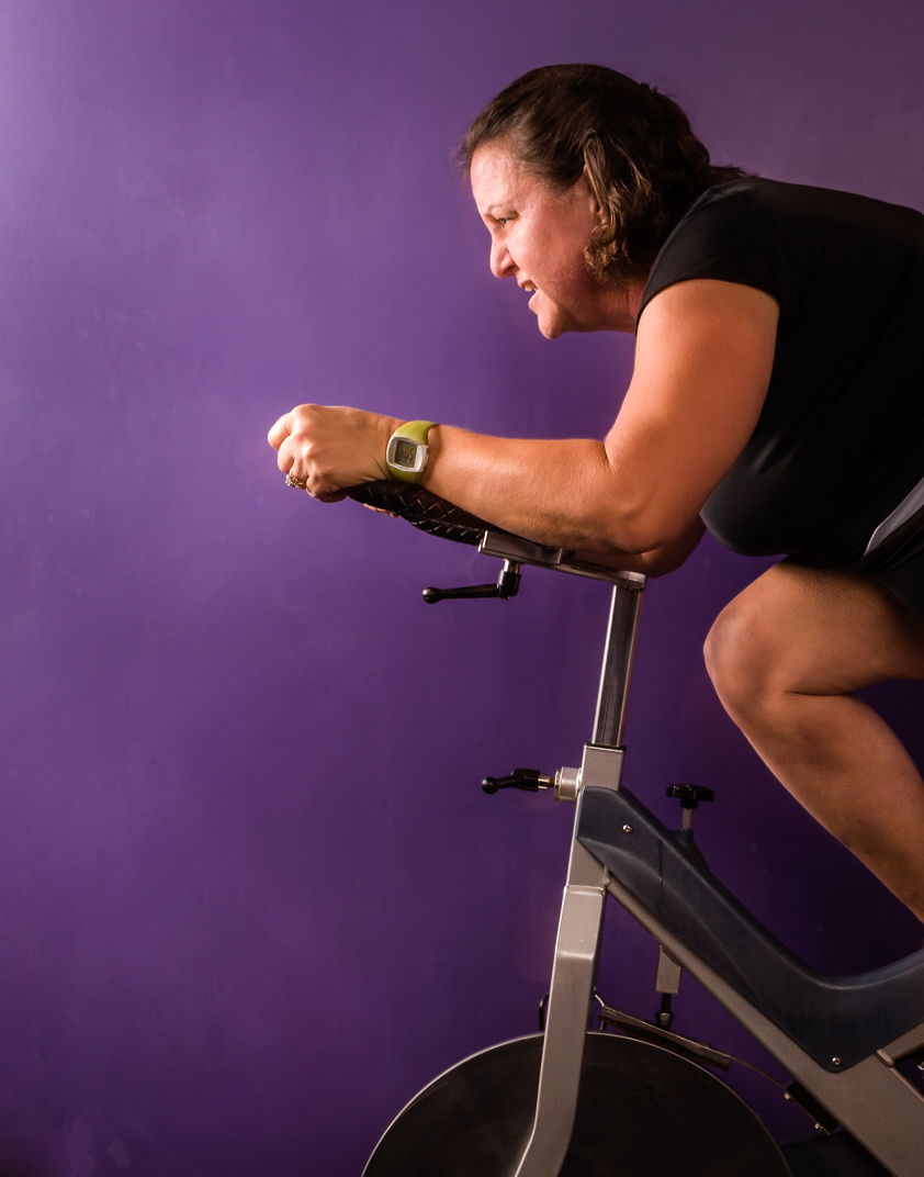 Connecticut woman with Multiple Sclerosis rides spinning bike against purple wall
