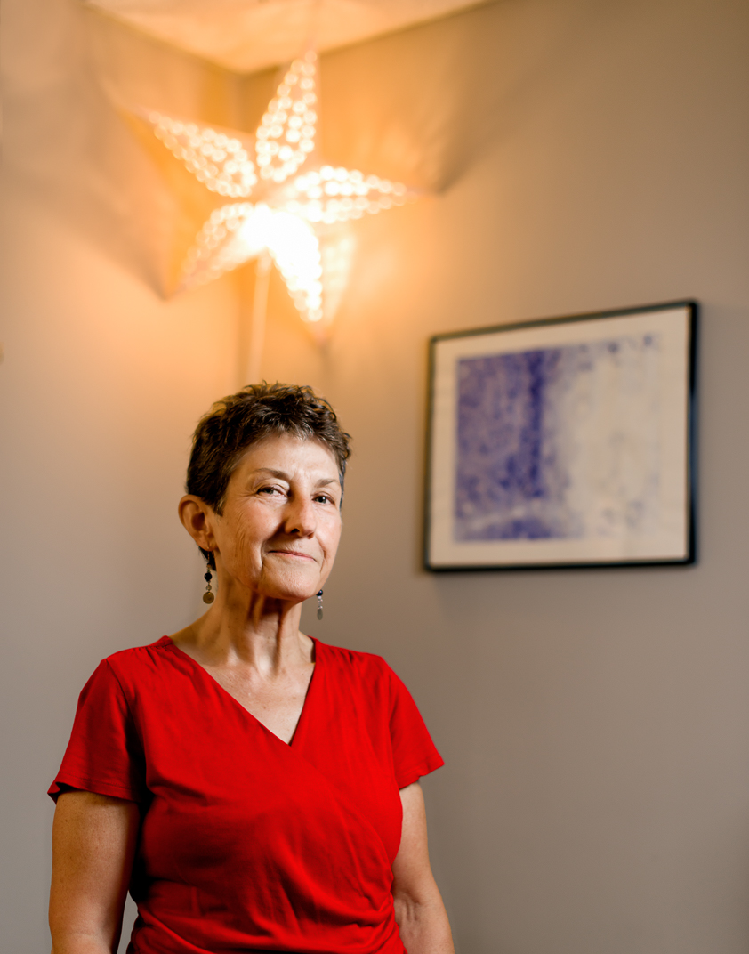 Woman in red shirt stands below star light next to blue painting