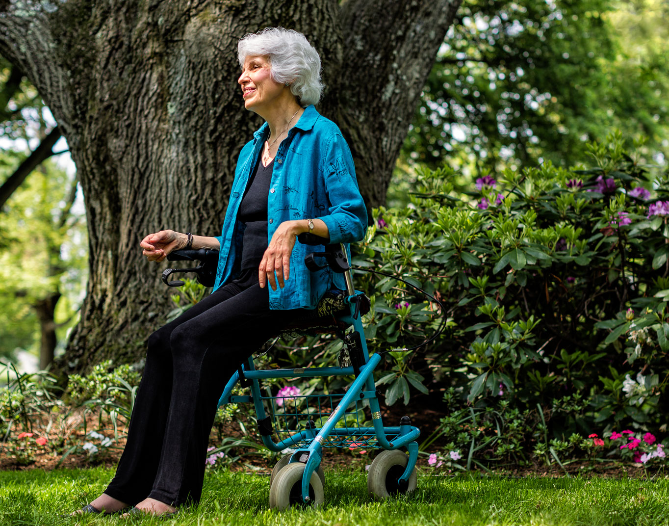 Connecticut older woman with Multiple Sclerosis meditates in garden next to large tree