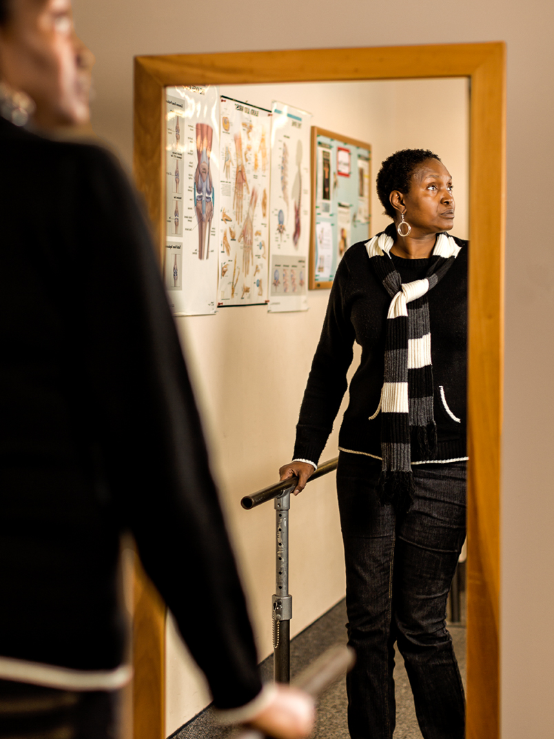 Connecticut African American woman with Multiple Sclerosis during physical therapy session reflected in mirror while hopefully looking off camera