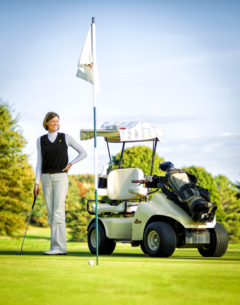 Woman stands on golf course with club and cart looking proud and confident