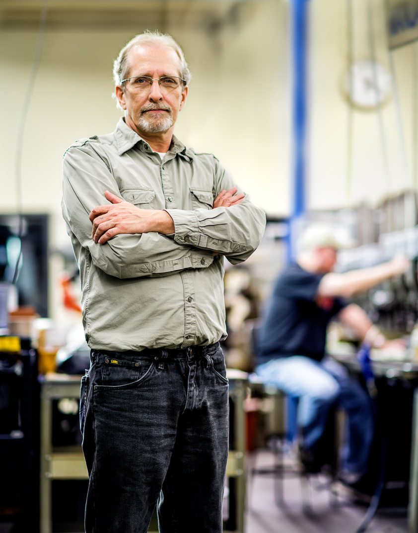 Connecticut man with Multiple Sclerosis stands with arms crossed in machine shop where he works