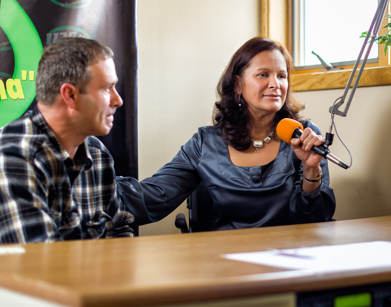 Connecticut woman with Multiple Sclerosis sits with husband while speaking to a Spanish radio station about her disease