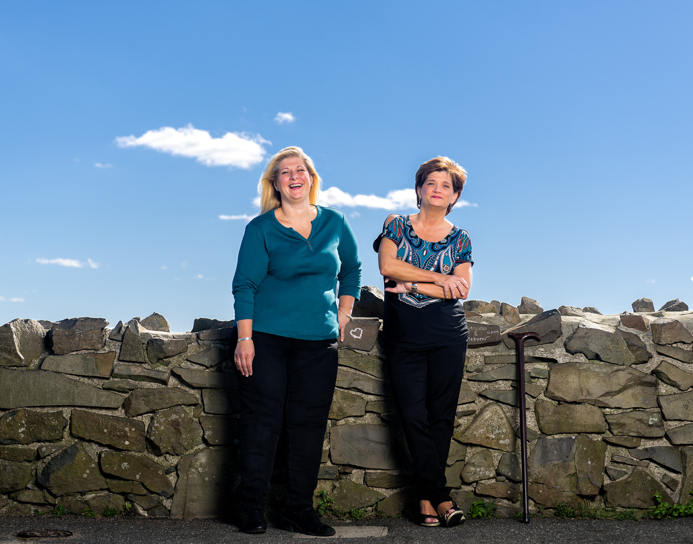 Connecticut woman with Multiple Sclerosis leans on stone wall with her sister
