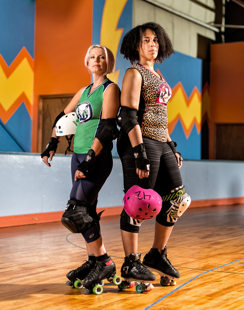 Two Connecticut women with Multiple Sclerosis proudly stand in roller derby uniforms and rollerskates at Ron-a-Roll in Vernon Connecticut