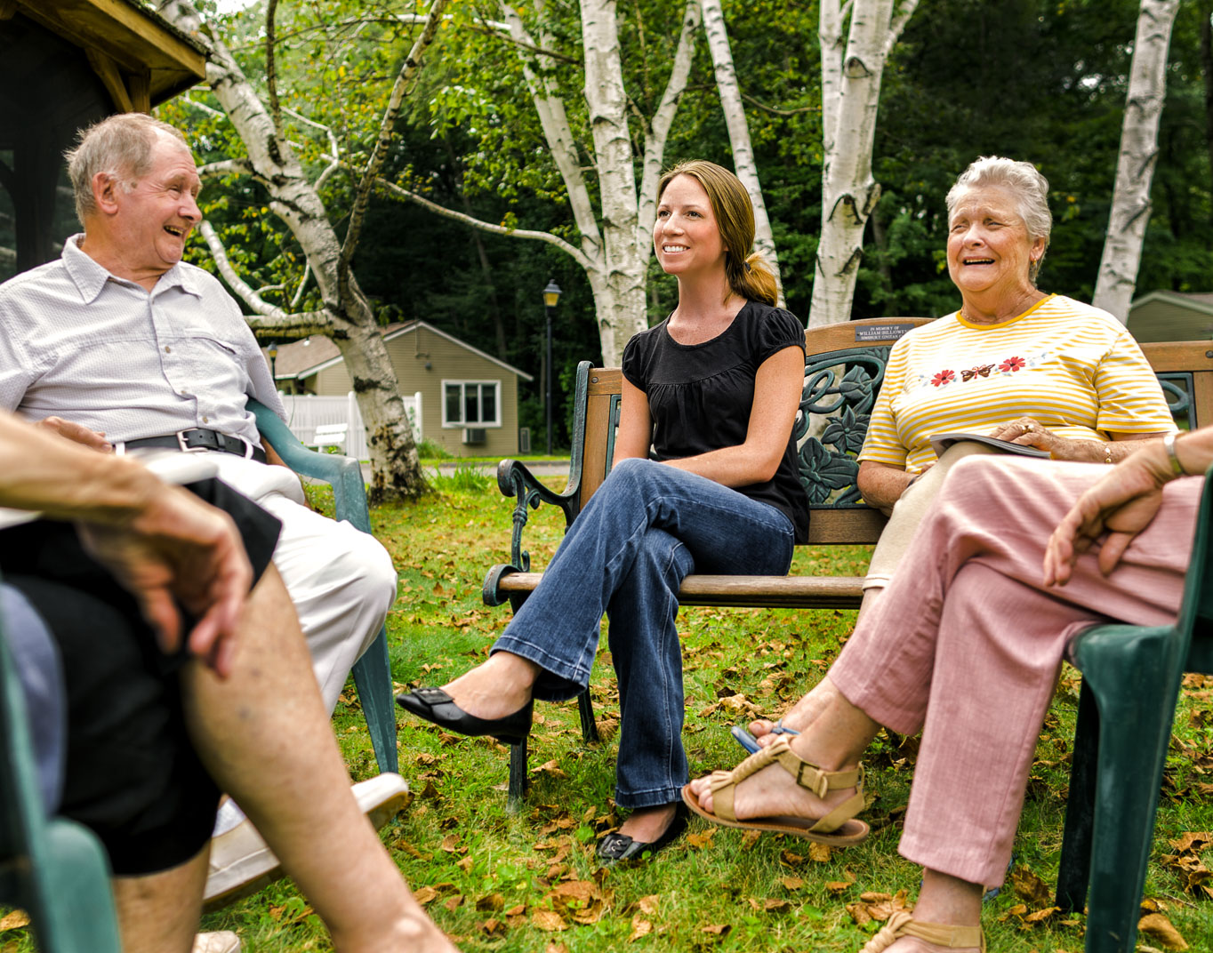 Young Connecticut woman with Multiple Sclerosis sits on park bench with friends in retirement community surrounded by birch trees