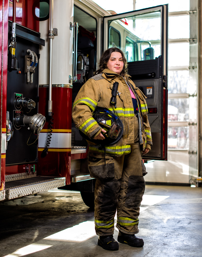 Connecticut woman with Multiple Sclerosis in her fire fighting gear standing next to firetruck