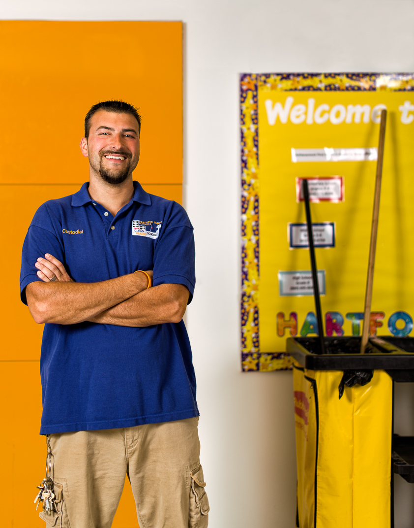 Connecticut man with Multiple Sclerosis stands with janitorial cart in elementary school