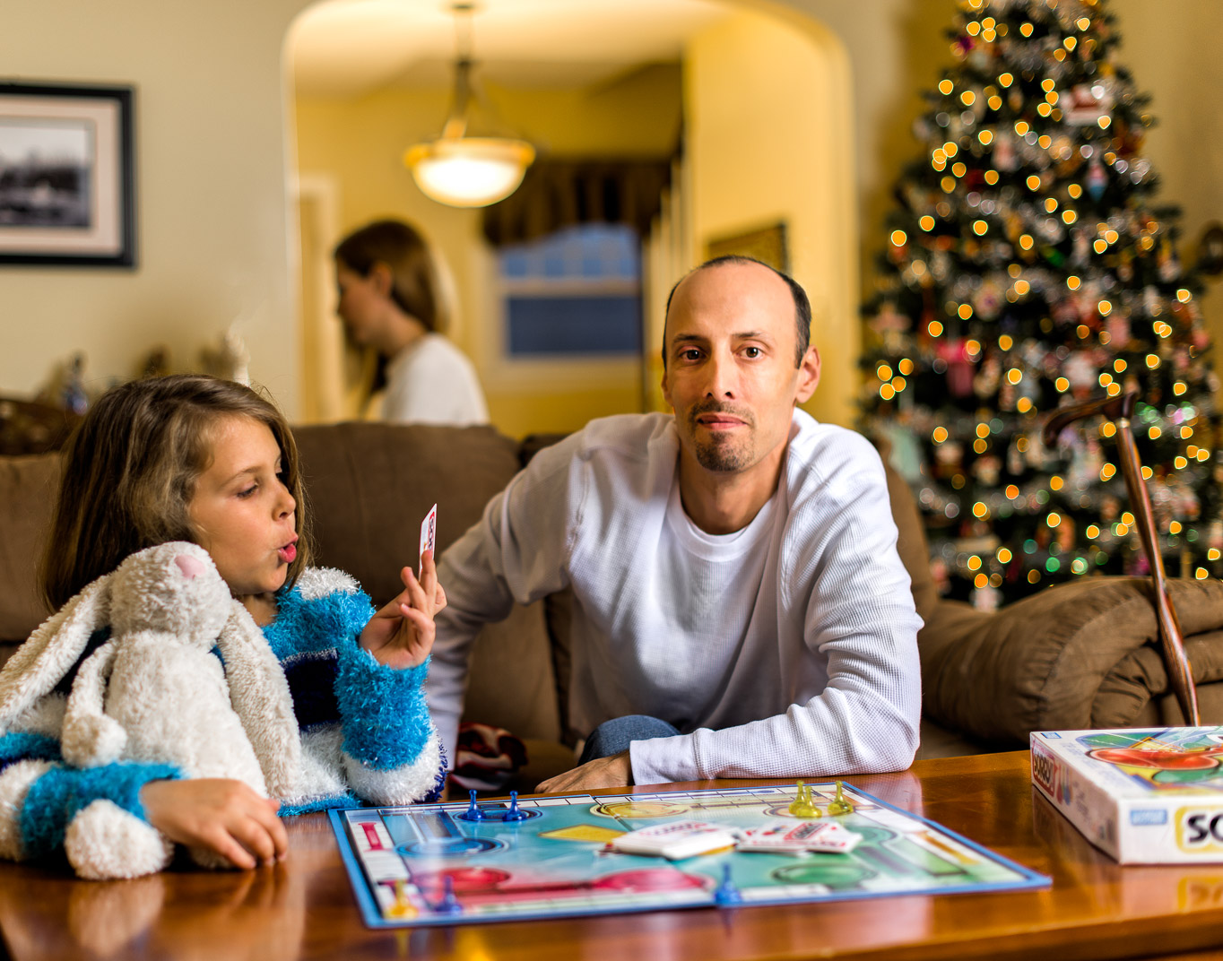 Connecticut man with Multiple Sclerosis plays Sorry with daughter in living room  while wife works at desk behind him near Christmas tree