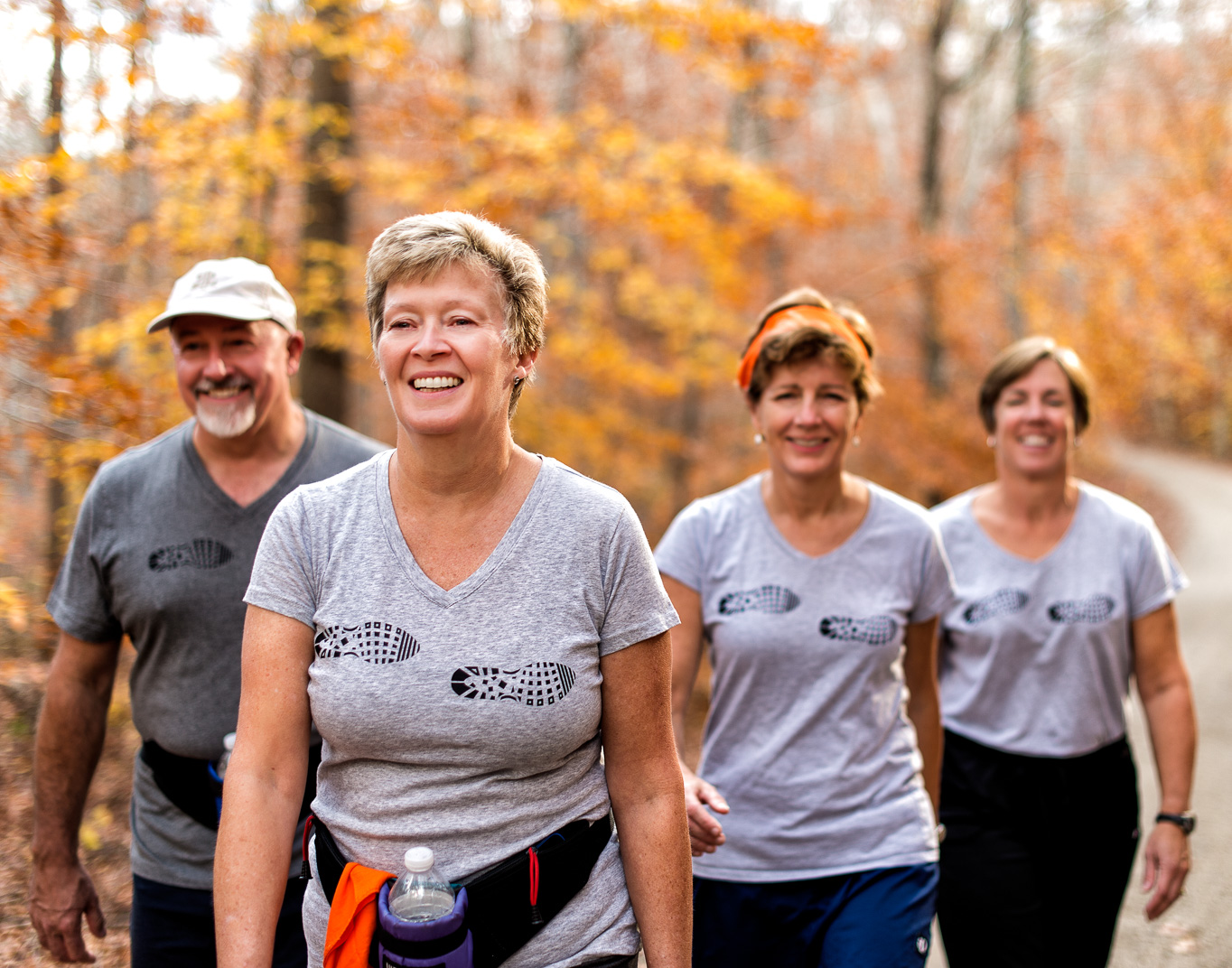 Connecticut woman with Multiple Sclerosis walks in woods on a fall day with walking team