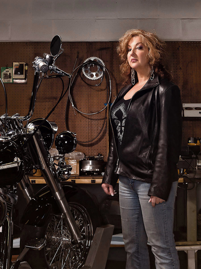 Woman in black leather jacket standing with motorcycle in garage