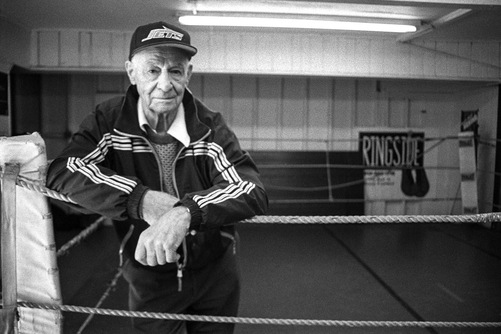 Black and white photograph of older man in Jets  hat leaning on ropes in boxing ring