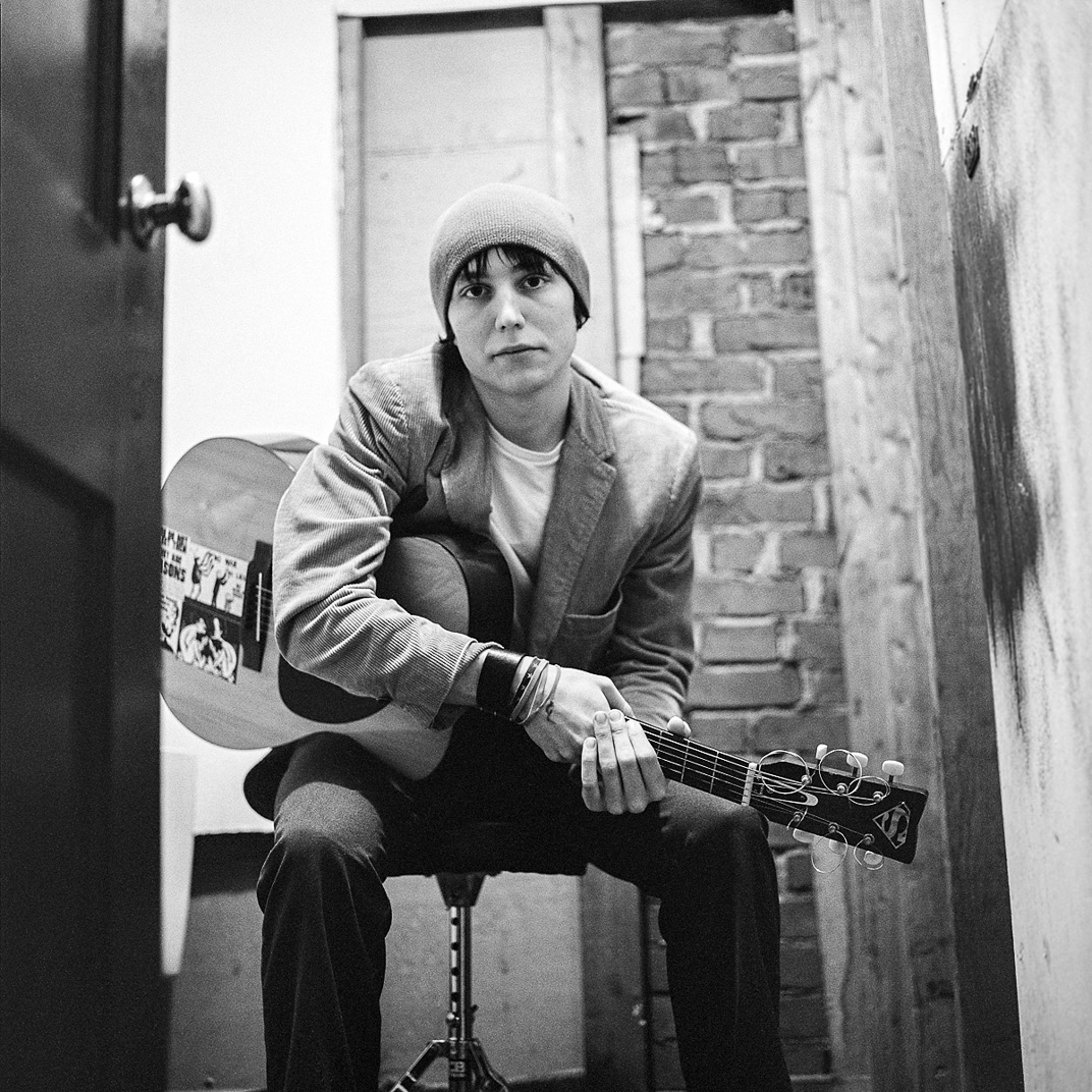 Black and white photograph of young male musician with guitar