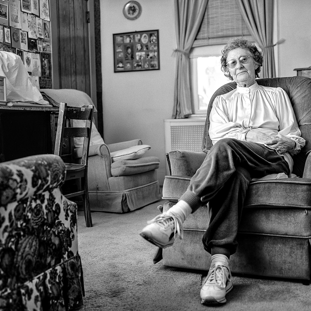 Black and white photograph of older woman with glasses sitting in velvet chair in living room