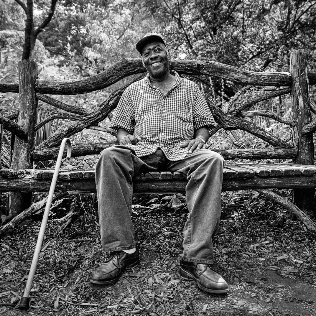 Black and white photograph of older African American man with cane sitting on bench in woods