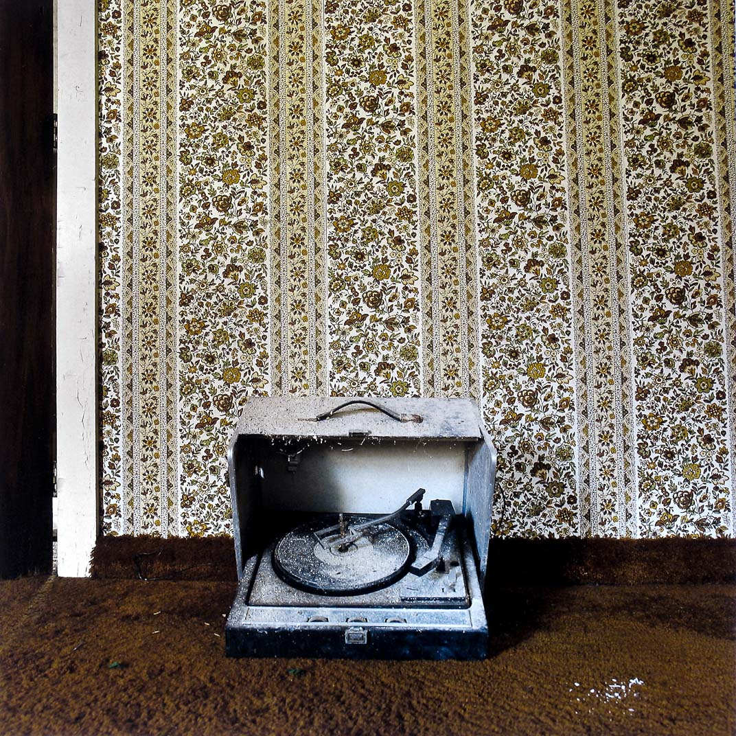Record player covered in dust sitting on brown plush carpet in front of vintage floral wallpaper