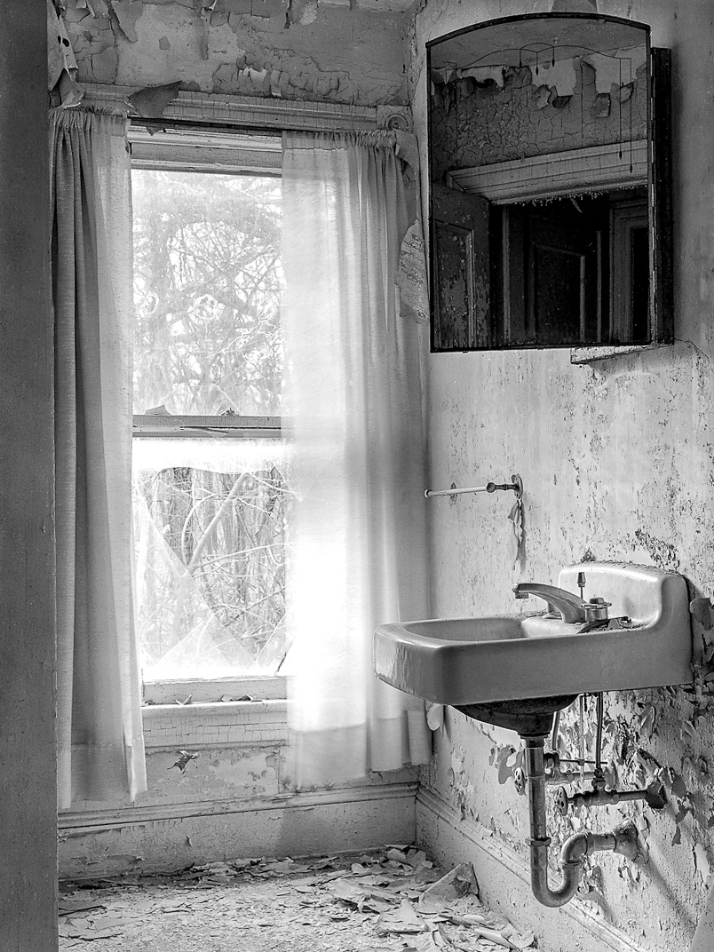 Bathroom with cast iron sink, hanging mirror, peeling paint and broken window