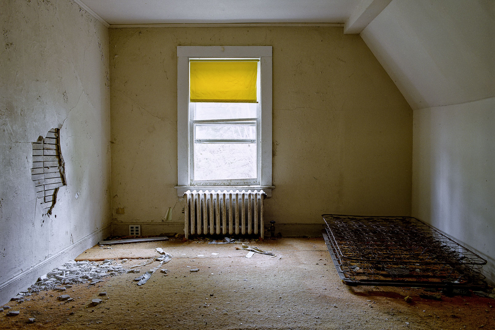 Mattress springs sitting on floor in empty bedroom with walls covered in dust and cobwebs and a yellow window shade