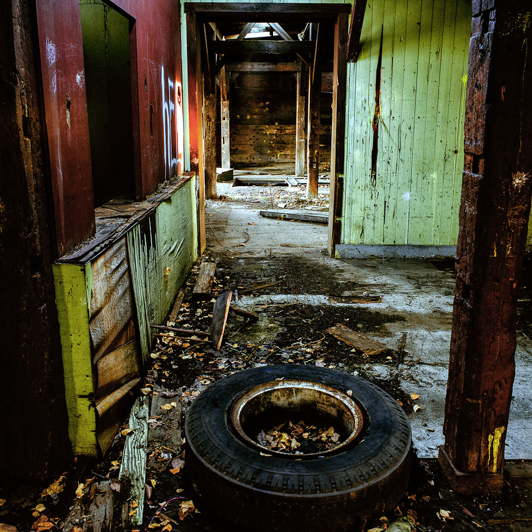 Old rubber tire laying on ground in dilapidated barn with red and green paint