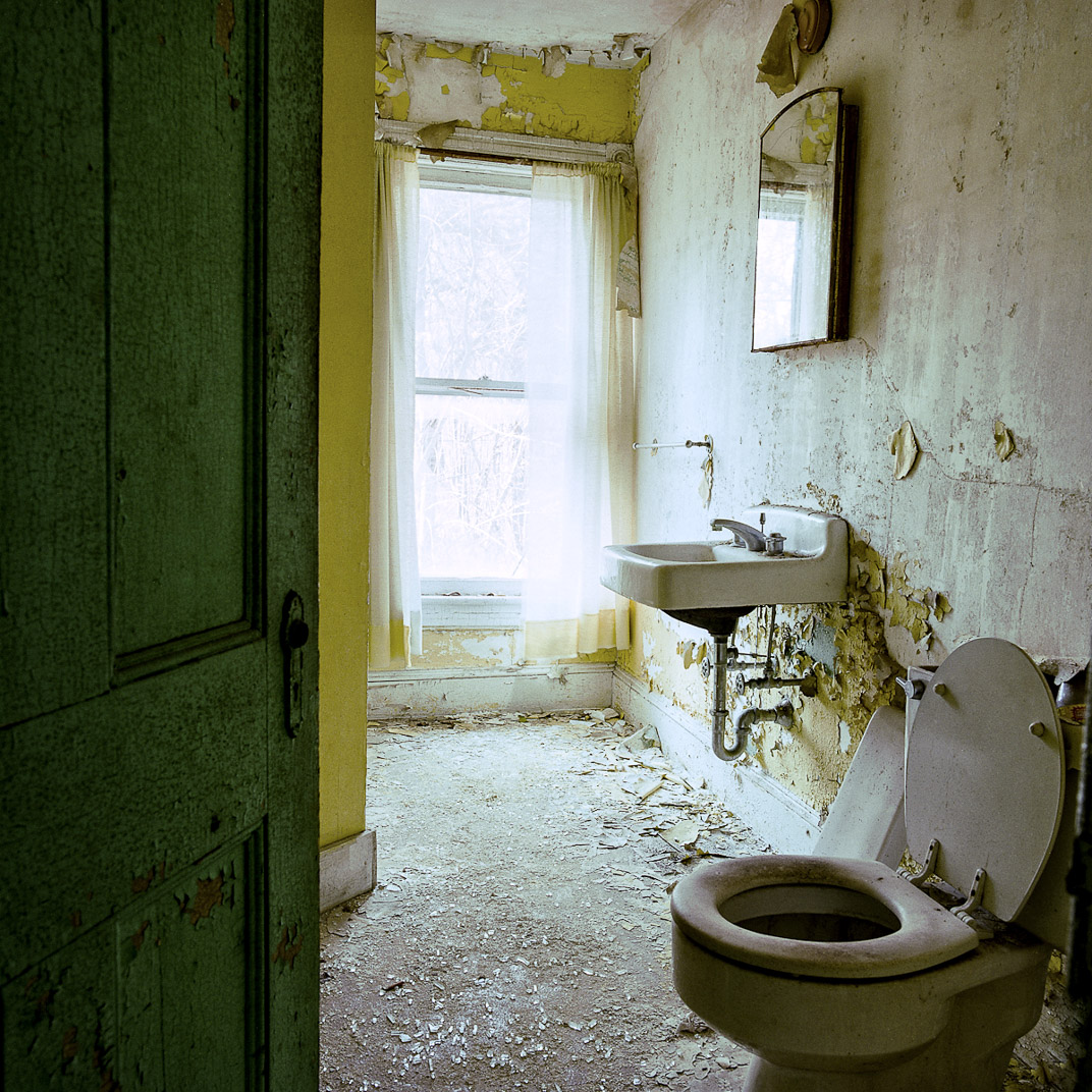 Green door with peeling paint leads into bright abandoned bathroom with yellow peeling paint
