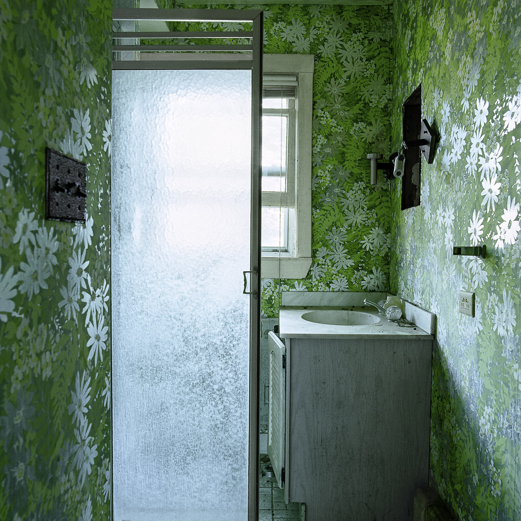 Vintage bathroom with bright green floral wallpaper and glass shower door