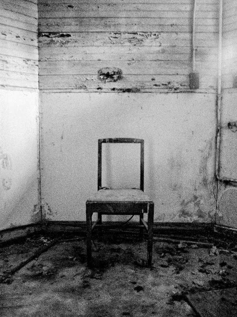 Black and white photograph of backless chair sitting in abandoned white room on dirty floor