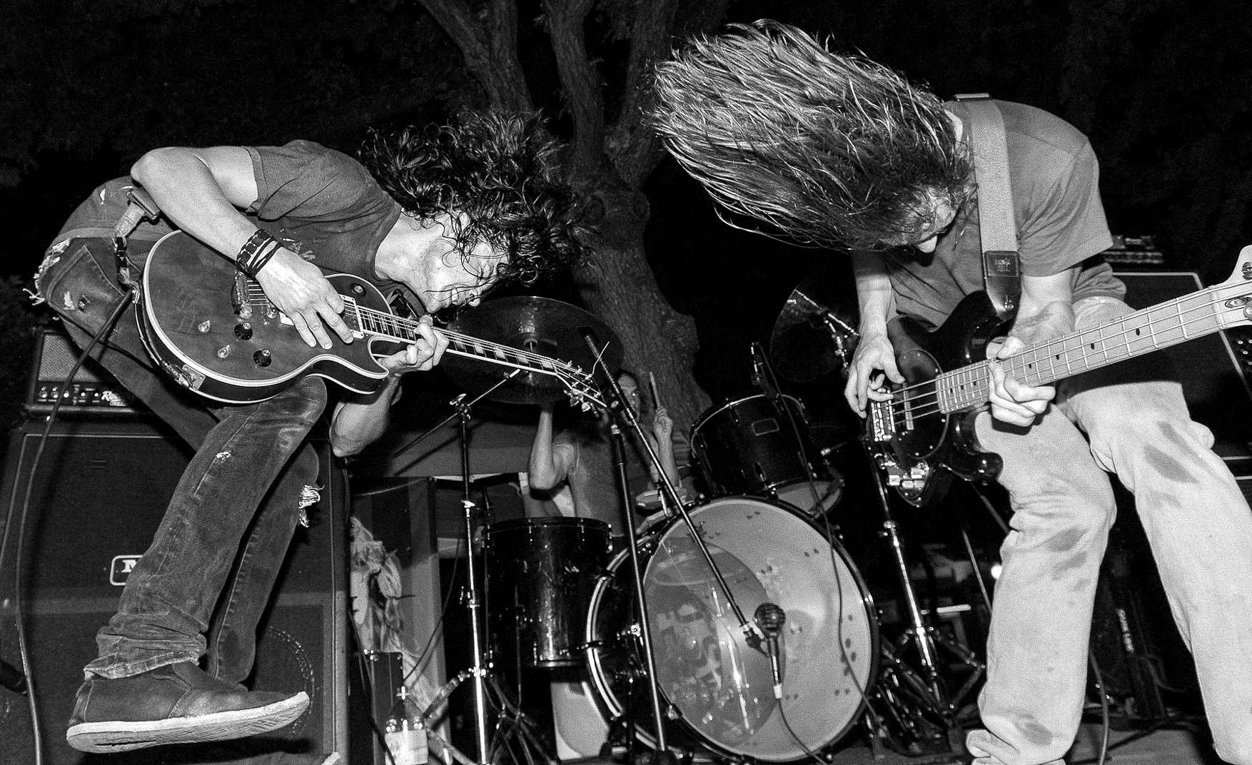Black and white photograph of Aloke  playing electric guitar and headbanging on stage