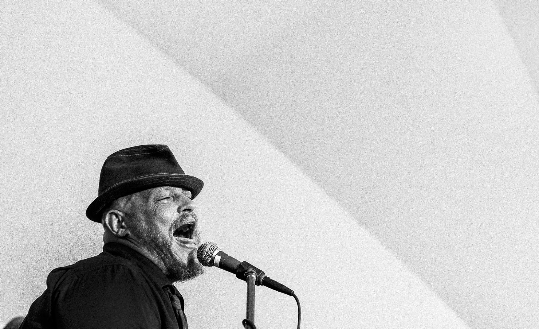 Black and white photograph of man with beard and mustache and black fedora hat singing loudly into microphone against white backdrop