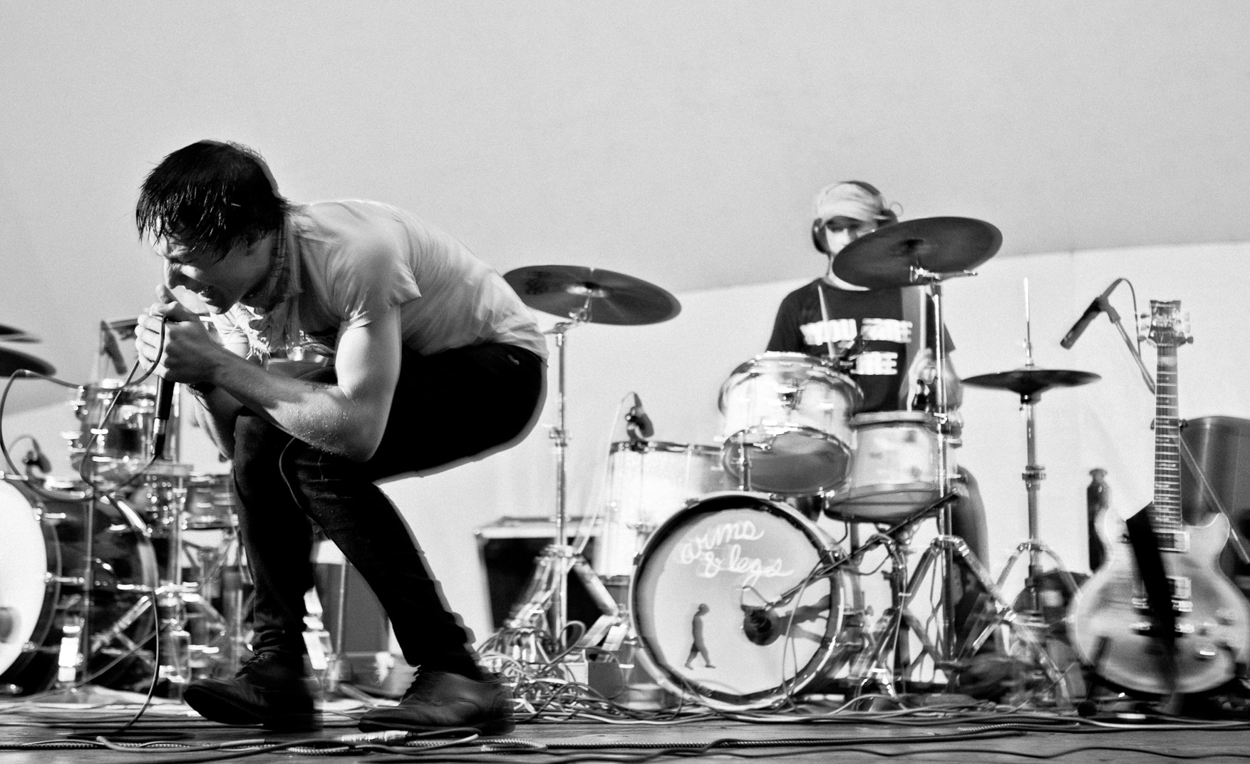 Black and white photograph of man on stage singing while kneeling down with drummer behind him