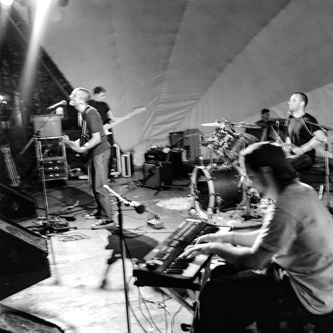 Black and white photograph of singer, keyboardist, drummer, and guitartist on large stage under white dome