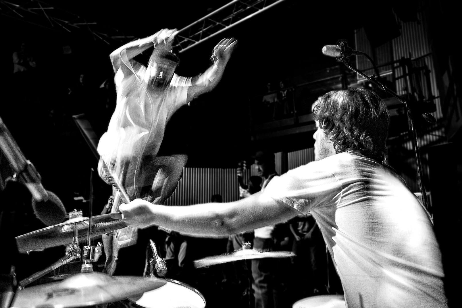 Black and white photograph of man jumping on stage with microphone in front of drummer