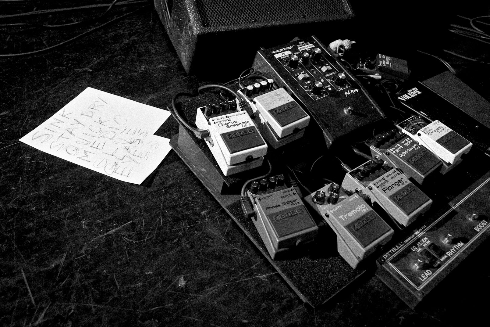 Black and white photograph of foot pedals with set list on stage floor