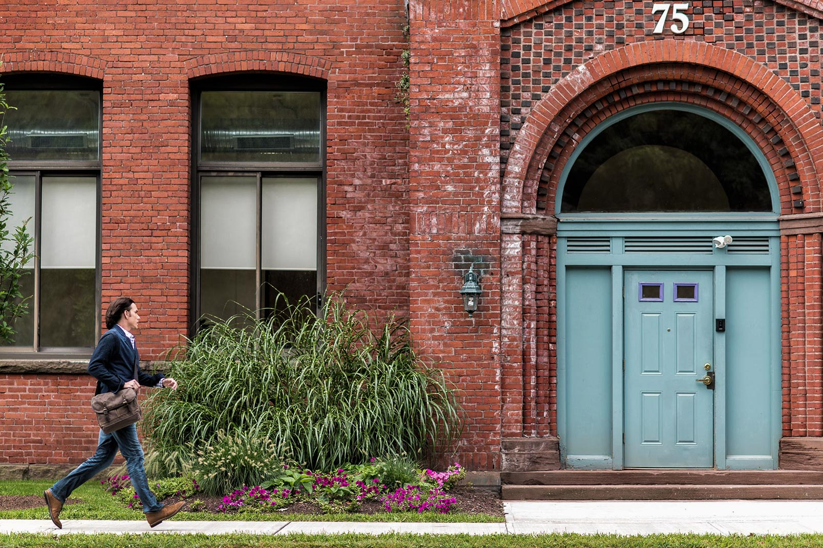 Man rushing to work at brick building with blue door in Hartford Connecticut