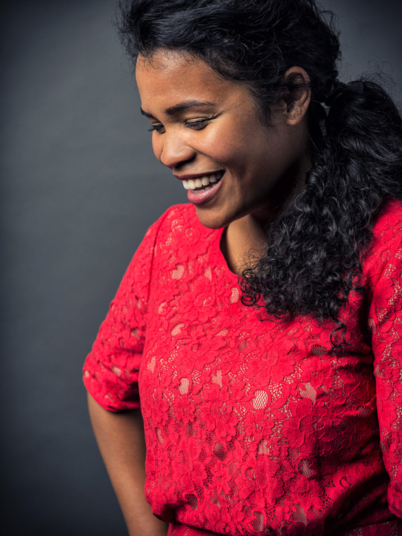 African American woman in red lace dress laughing against grey background