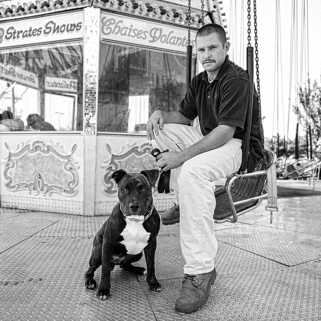 Black and white photograph of man on carnival swings with pitbull dog
