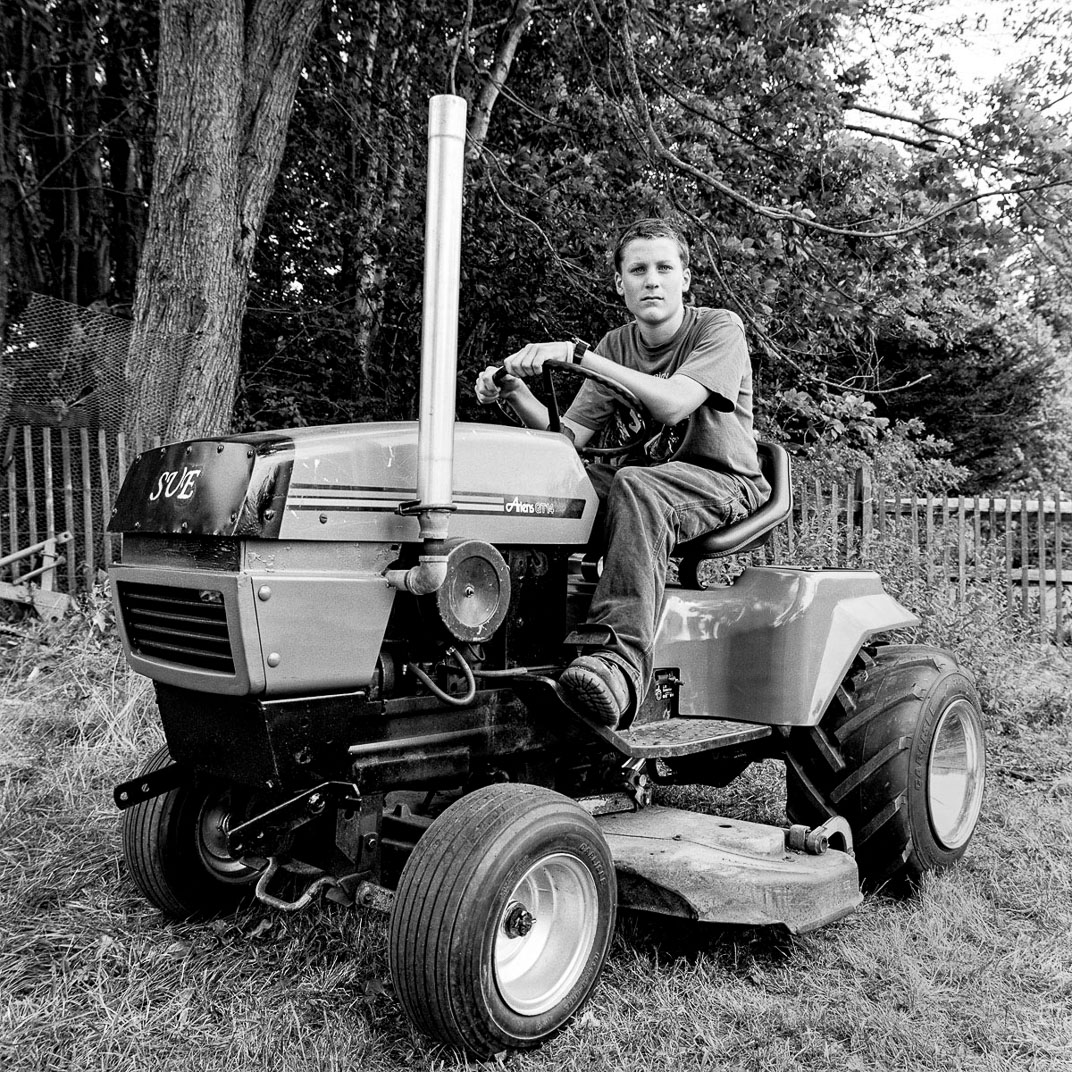 Black and white photograph of young man on lawn tractor