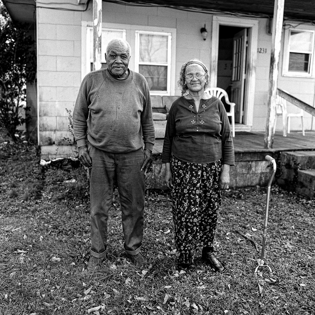 Black and white photograph of older African American couple standing in front of house