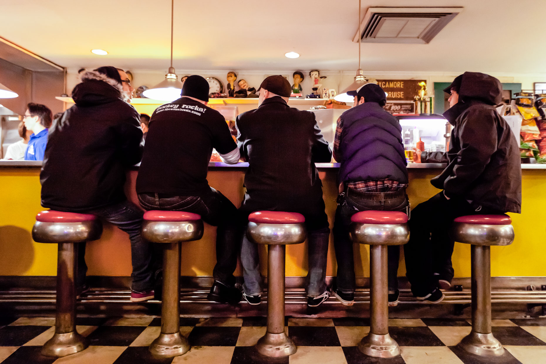 Group of men sitting on stools at counter in diner